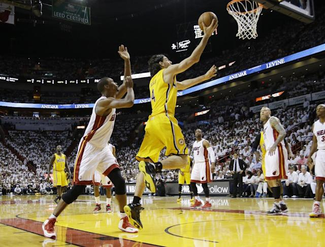 Indiana Pacers forward Luis Scola (4) drives to the basket past Miami Heat center Chris Bosh (1) during the first half of Game 3 in the NBA basketball Eastern Conference finals playoff series, Saturday, May 24, 2014, in Miami. (AP Photo/Lynne Sladky)