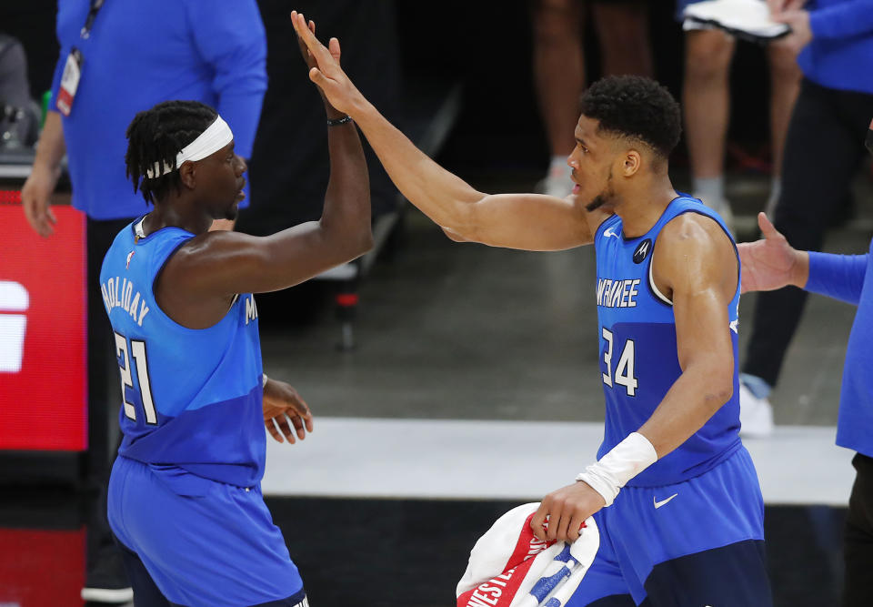 Giannis Antetokounmpo and Jrue Holiday high-five.