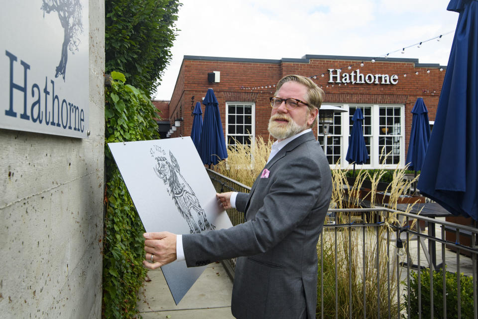 Hathorne restaurant owner John Stephenson holds a sign for a pop-up restaurant which will cover the Hathorne sign when that restaurant is open, Wednesday, Aug. 18, 2021, in Nashville, Tenn. Stephenson hosts temporary restaurants, known as pop-ups which he lets use his space, in an effort to help them weather the pandemic. Most recently, Hathorne hosts the pop-up St. Vito Focacciaria pizza company, which sign he holds, every Sunday night. (AP Photo/John Amis)