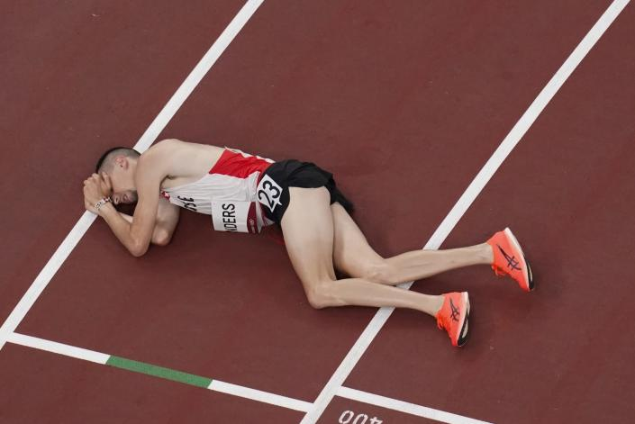 Julien Wanders, of Switzerland, collapses after running in the men's 10,000-meter finals at the 2020 Summer Olympics, Friday, July 30, 2021, in Tokyo. (AP Photo/Morry Gash)