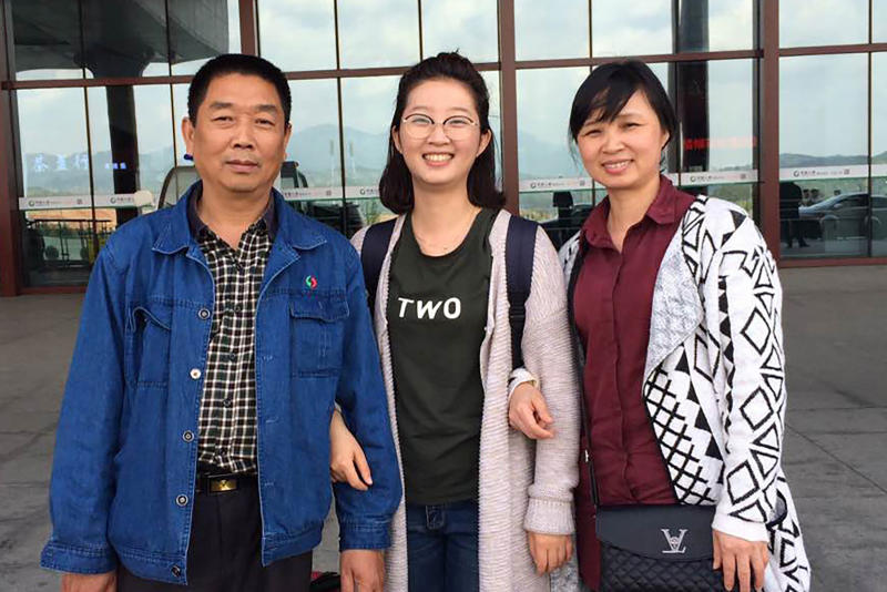FILE - This 2017 file photo provided by Xinyang Zhang shows his sister, Yingying, with their parents, Ronggao Zhang, right, and Lifeng Ye, at a train station in Nanping, China. The 26-year-old visiting scholar at the University of Illinois at Urbana-Champaign, disappeared June 9, 2017. Brendt Christensen, a former graduate student, has been charged with kidnapping and killing her. Zhang's body has not been found.  (Xinyang Zhang via AP, File)