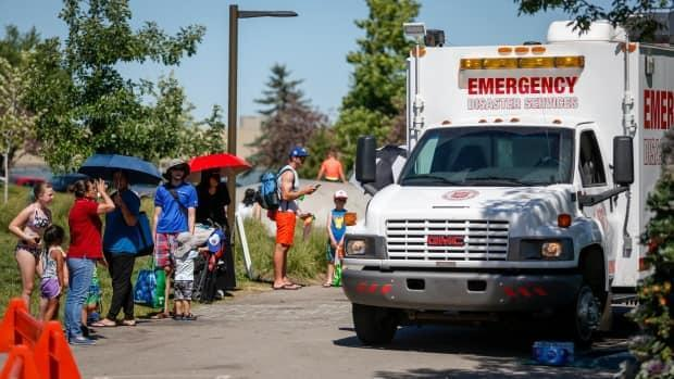 A Salvation Army emergency services vehicle is set up as a cooling station as people line up to get into a splash park while trying to beat the heat in Calgary, on June 30. Alberta is due for another wave of hot weather this weekend. (Jeff McIntosh/Canadian Press - image credit)