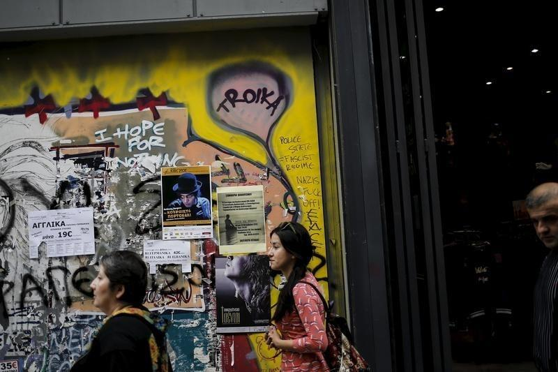 """People walk along the commercial Ermou street next to graffiti reading """"Troika"""" in central Athens"""