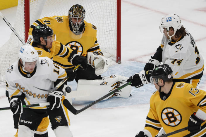 Pittsburgh Penguins' Mark Jankowski (14) deflects a puck that scored on Boston Bruins goaltender Jaroslav Halak during the first period of an NHL hockey game Saturday, April 3, 2021, in Boston. (AP Photo/Winslow Townson)