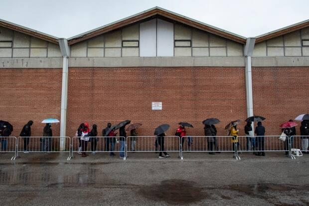 People line up in the rain outside Downsview Arena in northwest Toronto on April 29, 2021 to get a COVID-19. The city says mobile and pop-up clinics in hot spot neighbourhoods will continue.