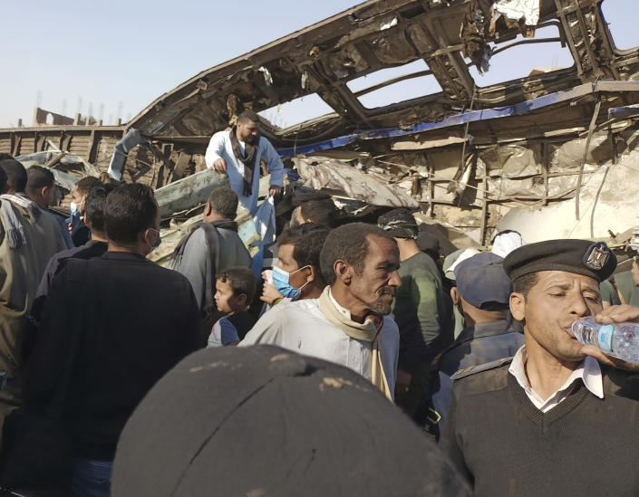 An Egyptian policeman drinks water as villagers look for remains of victims around mangled train carriages at the scene of a train accident in Sohag,Egypt, Friday, March 26, 2021. Egyptian officials say two trains collided in southern Egypt in the latest in a series of deadly accidents along Egypt's troubled rail system, which has been plagued by poor maintenance and management. (AP Photo)