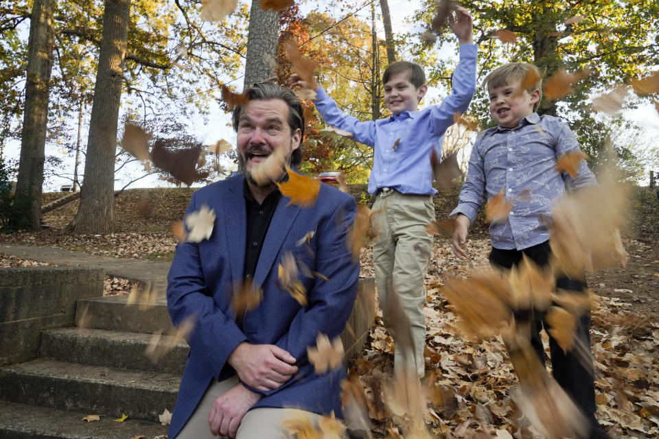 Christopher Hughey poses for a picture with his sons, Henry, 5, Harrison, 9, on Saturday, Nov. 21, 2020, in Charlotte, N.C. (AP Photo/Chris Carlson)