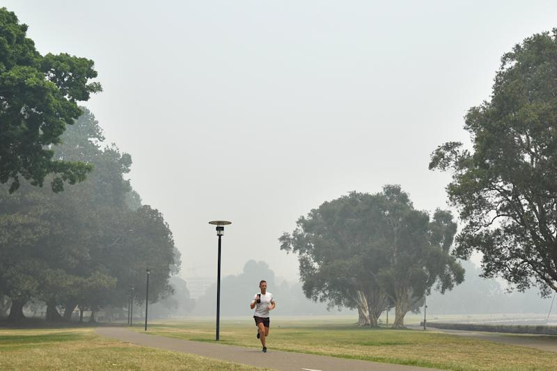 A man runs through Rushcutters Bay Park as smoke haze from bushfires in New South Wales blankets the CBD in Sydney.