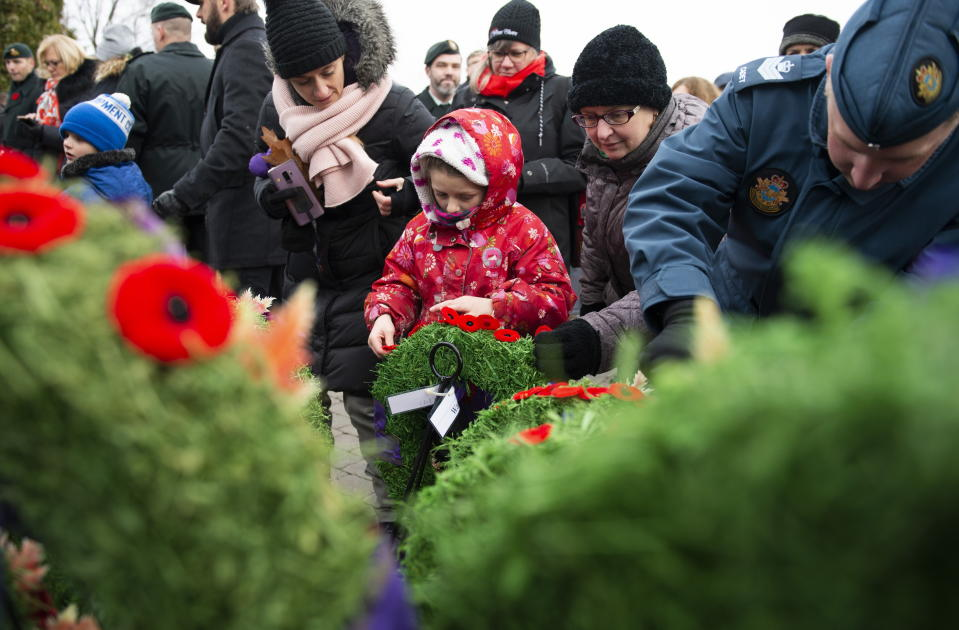 People pin poppies on wreaths at the National Military Cemetery at Beechwood Cemetery following a Remembrance Day ceremony in Ottawa, on Monday, Nov. 11, 2019. THE CANADIAN PRESS/Justin Tang