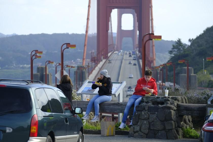 People eat while sitting at a vista point by the Golden Gate Bridge Friday, March 27, 2020, in Sausalito, Calif. The surge of coronavirus cases in California that health officials have warned was coming has arrived and will worsen, Gov. Gavin Newsom said Friday, while the mayor of Los Angeles warned that by early next week his city could see the kind of crush that has crippled New York.(AP Photo/Eric Risberg)