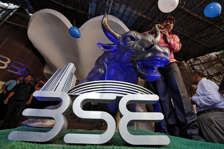 FILE PHOTO: A man ties a balloon to the horns of a bull statue at the entrance of the BSE while celebrating the Sensex index rising to over 30,000, in Mumbai