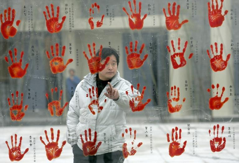 A visitor looks at the enlarged handprints of Chinese soldiers from World War Two during a visit to the Anti-Japanese War Museum in Dayi County, Sichuan province