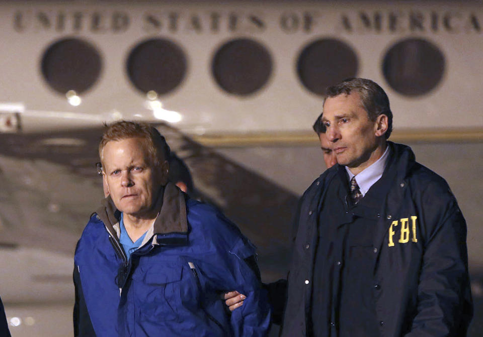 FILE - In this Dec. 5, 2017, file photo, fugitive lawyer Eric Conn, left, is taken into custody by FBI agents on the tarmac at Blue Grass Airport in Lexington, Ky. A class action lawsuit has been filed Friday, Sept. 20. 2019, on behalf of a group of people who lost federal disability benefits after their lawyer, Coon, was arrested for fraud. (AP Photo/Matt Goins, File)