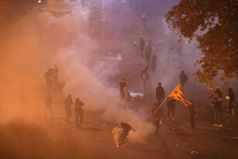 Protesters are dispersed by teargas thrown by national police officers, during clashes in Barcelona, Spain, Friday, Oct. 18, 2019.The Catalan regional capital is bracing for a fifth day of protests over the conviction of a dozen Catalan independence leaders. Five marches of tens of thousands from inland towns are converging in Barcelona's center for a mass protest. (AP Photo/Emilio Morenatti)