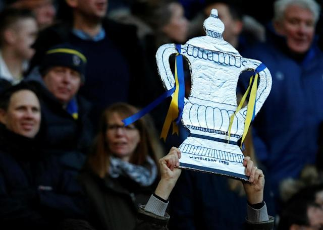 An AFC Wimbledon fan holds up a handmade replica of the FA Cup trophy during the English FA Cup third round match between Tottenham and AFC Wimbledon at Wembley Stadium in London, on January 7, 2018 (AFP Photo/)