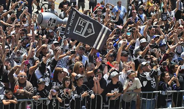 Fans of the Los Angeles Kings NHL hockey team cheer as the team rides by with the Stanley Cup trophy during a parade, Monday, June 16, 2014, in Los Angeles. The parade and rally were held to celebrate the Kings' second Stanley Cup championship in three seasons. The Kings defeated the New York Rangers for the title. (AP Photo/Mark J. Terrill)