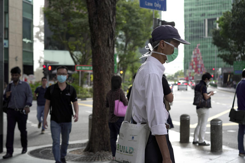SINGAPORE, SINGAPORE - FEBRUARY 28: People wearing masks wait at a traffic junction at the Central Business District on February 28, 2020 in Singapore. The coronavirus, originating in Wuhan, China has spread to over 80,000 people globally, more than 50 countries have now been infected. (Photo by Ore Huiying/Getty Images)