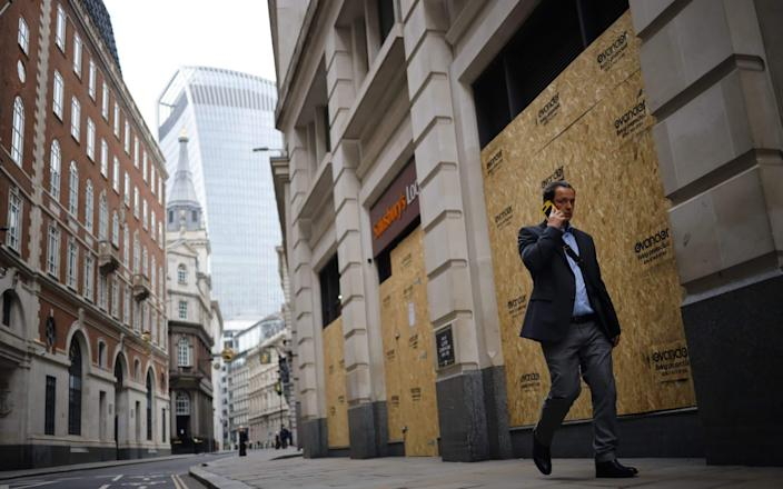 A worker walks through an all but deserted City of London during the first lockdown. Last year, Boris Johnson was at pains to encourage people back to the office amid dire predictions about the cost of them staying away - Tolga Akmen/AFP