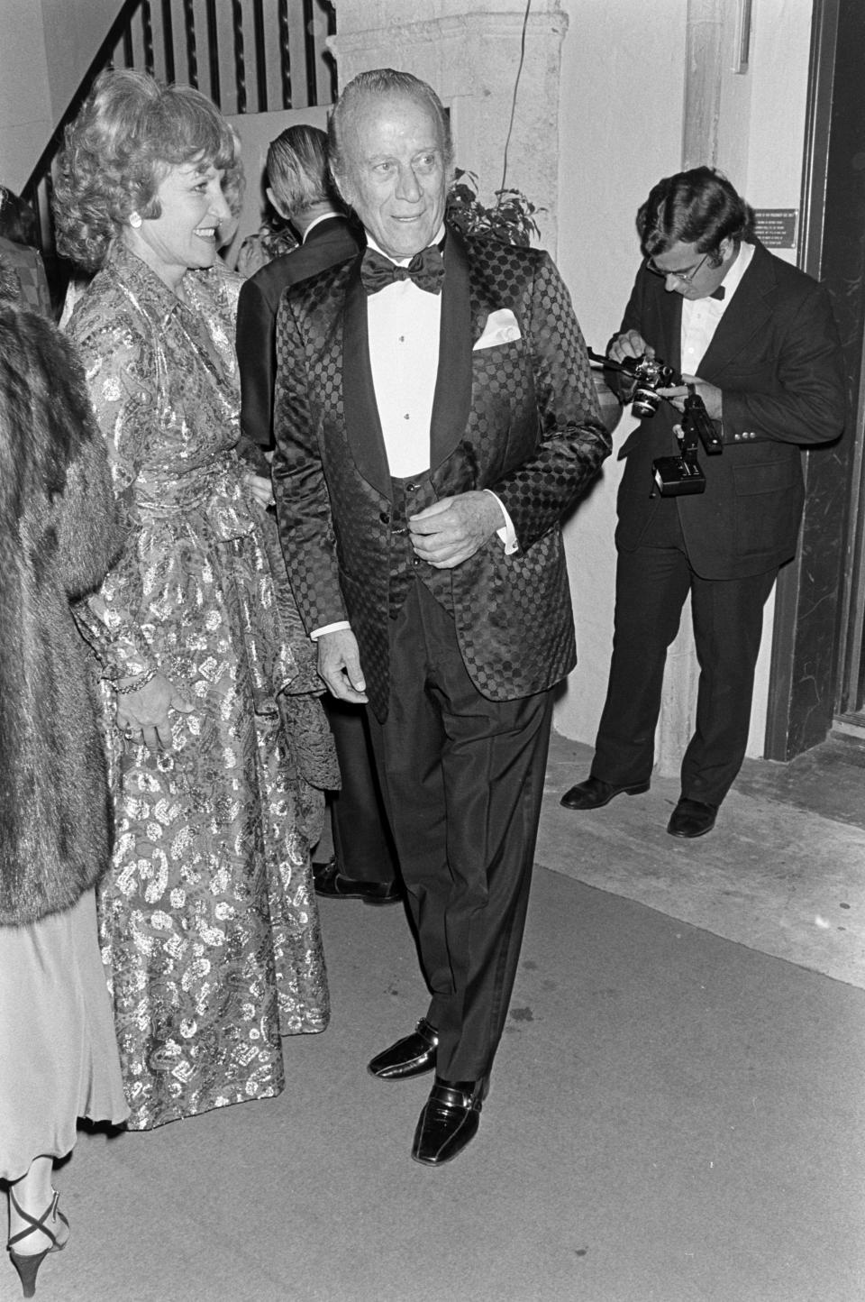 Aldo Gucci in a blue brocade Gucci evening coat greets guest during reception at his Palm Beach, Fla., home on Dec. 2, 1979. - Credit: WWD