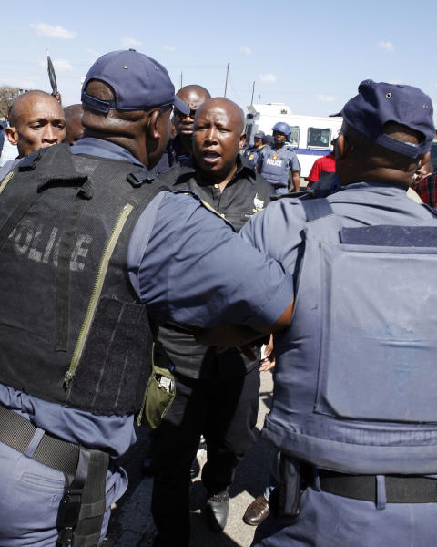 Firebrand politician Julius Malema, centre, argues with police officers, at Lonmin Platinum Mine near Rustenburg, South Africa, Monday, Sept. 17, 2012. London-registered Lonmin PLC announced it is halting construction of a new shaft, putting 1,200 people out of work, as the bloody and bitter strike at its beleaguered South African platinum mine dragged on its fifth week. The strikes that have halted work at seven gold and platinum mines have spread to the chrome sector, according to the official South African Press Association. Meanwhile, police blocked rabblerousing politician Julius Malema from addressing some 3,000 strikers gathered at a stadium at the Lonmin mine at Marikana, northwest of Johannesburg. (AP Photo/Themba Hadebe)