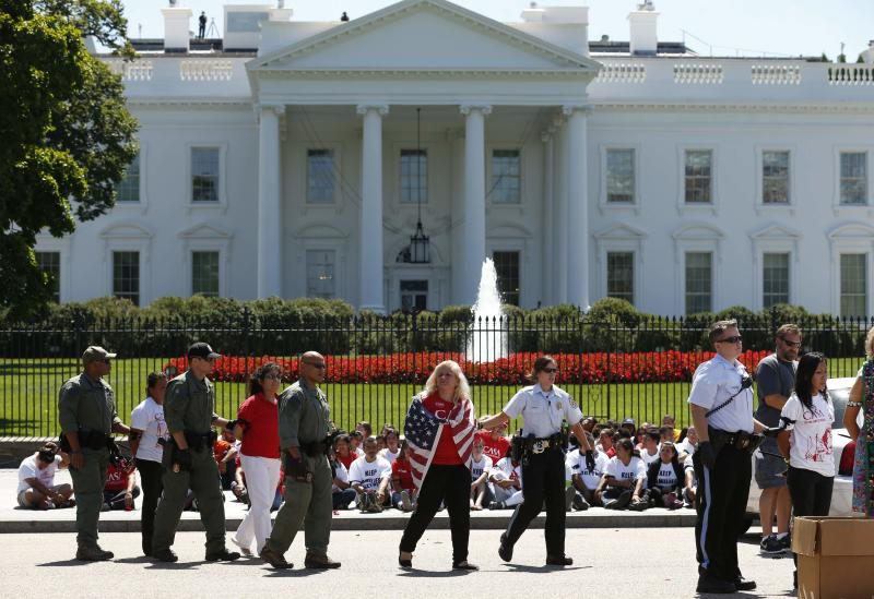 An anti-deportation protester wearing a U.S. flag is arrested with others during a demonstration in front of the White House in Washington