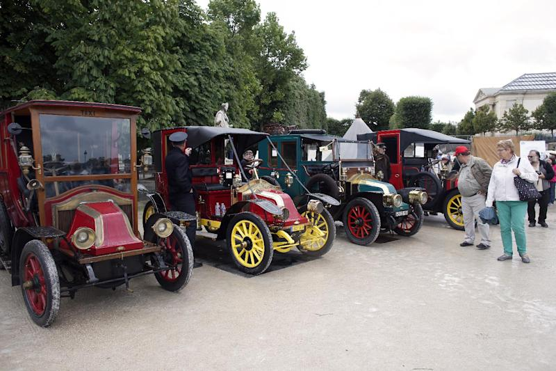 People look at vintage Renault taxis, the same models used to transport French troops from Paris to the First Battle of the Marne in 1914, at a WWI military camp reconstruction in Paris on July 13, 2014 (AFP Photo/Thomas Samson)