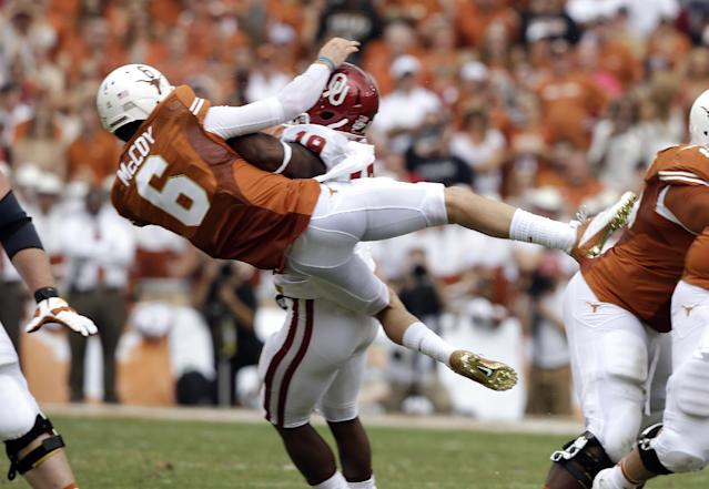 Texas quarterback Case McCoy (6) is knocked off his feet Oklahoma linebacker Eric Striker (19) after releasing a pass during the first half of an NCAA college football game at the Cotton Bowl Saturday, Oct. 12, 2013, in Dallas. (AP Photo/LM Otero)
