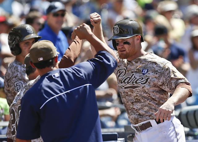 San Diego Padres' Brooks Conrad is greeted at the dugout after his solo home run against the San Francisco Giants in the seventh inning of a baseball game Sunday, July 6, 2014, in San Diego. (AP Photo/Lenny Ignelzi)