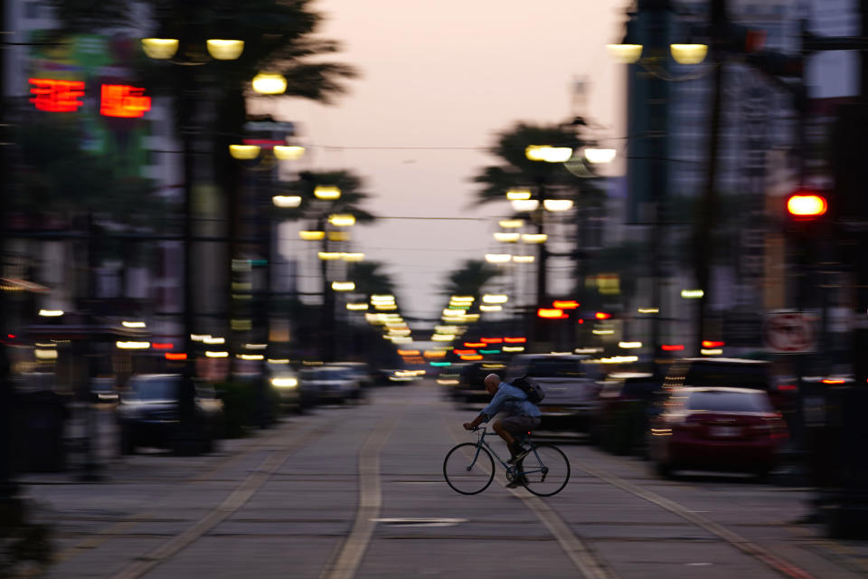 In the aftermath of Hurricane Ida, a man rides his bike across Canal Street, Saturday, Sept. 4, 2021, in the French Quarter of New Orleans. (AP Photo/Matt Slocum)