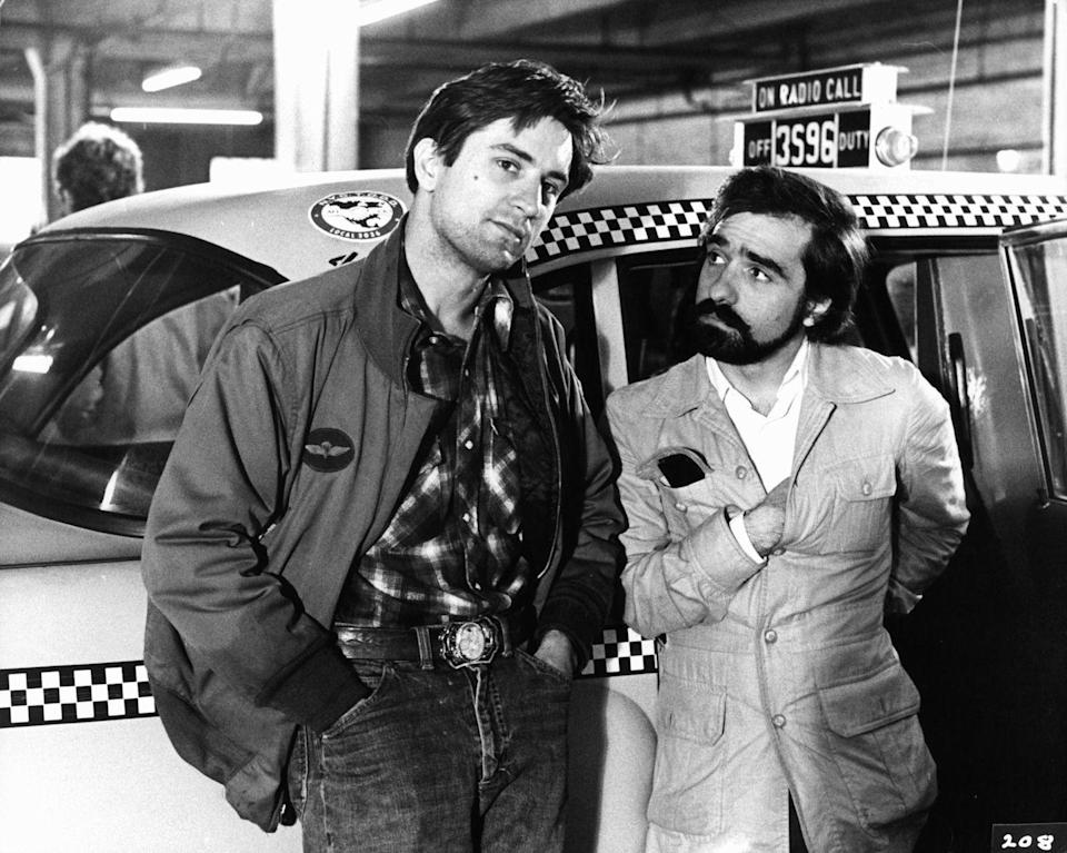 "<p>A young Robert De Niro and Martin Scorsese discuss a scene before filming on the set of <em>Taxi Driver</em>. De Niro reportedly worked 15-hour days for a month <a href=""https://www.imdb.com/title/tt0075314/trivia"" rel=""nofollow noopener"" target=""_blank"" data-ylk=""slk:driving cabs"" class=""link rapid-noclick-resp"">driving cabs</a> to prepare for his role.</p>"