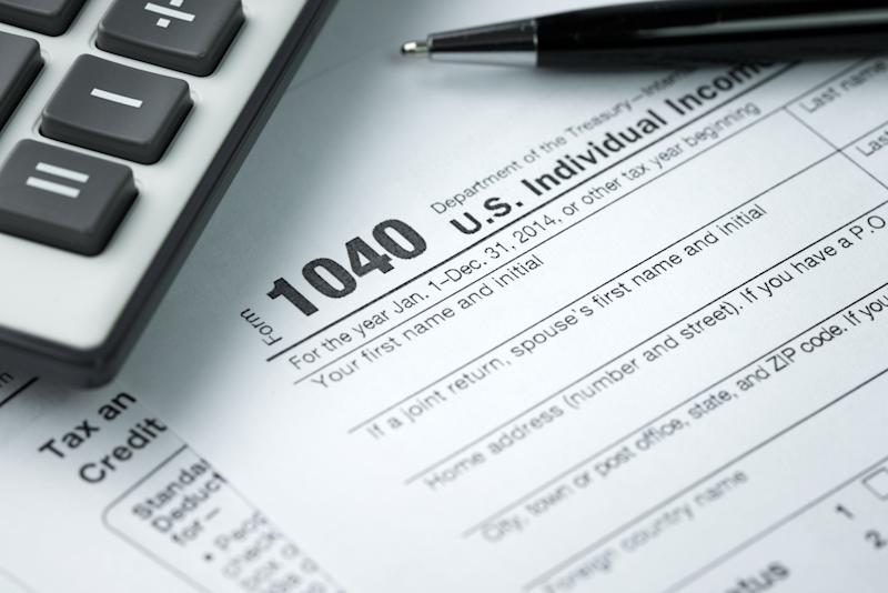 IRS tax form 1040 next to pen and calculator