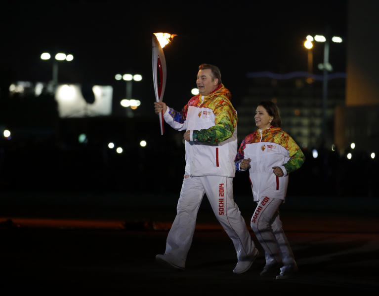 Irina Rodnina and Vladislav Tretiak run before lighting the Olympic cauldron during the opening ceremony of the 2014 Winter Olympics in Sochi, Russia, Friday, Feb. 7, 2014. (AP Photo/Matt Slocum, Pool)