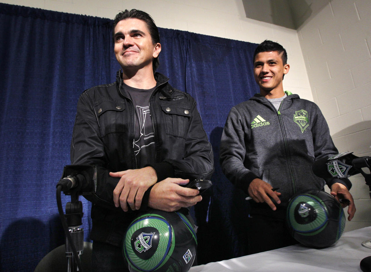 "Latin musician Juanes, left, and Seattle Sounders FC forward Fredy Montero smiles following a news conference about Juanes upcoming tour Tuesday, March 8, 2011, in Seattle. Juanes kicks-off his world ""P.A.R.C.E. Tour"" Thursday March 10, in Seattle."