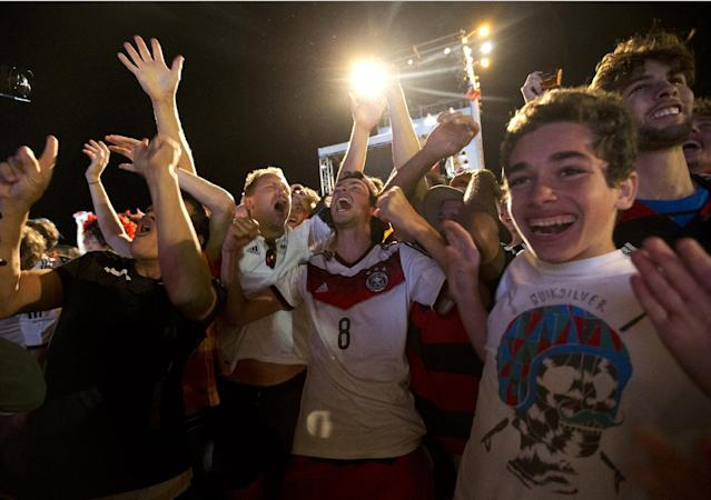 Soccer fans of the Germany national soccer team celebrate their team's victory during a live broadcast of the soccer World Cup match between Germany and Argentina, inside the FIFA Fan Fest area on Copacabana beach, Rio de Janeiro, Brazil, Sunday, July 13, 2014. Mario Goetze volleyed in the winning goal in extra time to give Germany its fourth World Cup title with a 1-0 victory over Argentina. (AP Photo/Silvia Izquierdo)