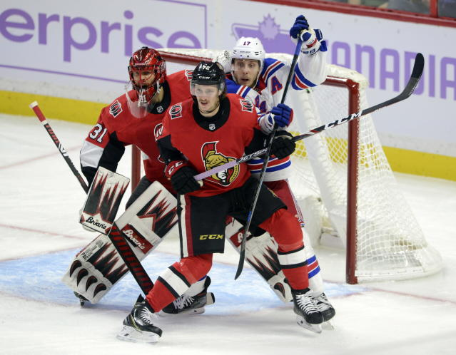Ottawa Senators goaltender Anders Nilsson (31) guards the net as defenseman Thomas Chabot (72) holds off New York Rangers right wing Jesper Fast (17) during the first period of an NHL hockey game Friday, Nov. 22, 2019, in Ottawa, Ontario. (Sean Kilpatrick/The Canadian Press via AP)
