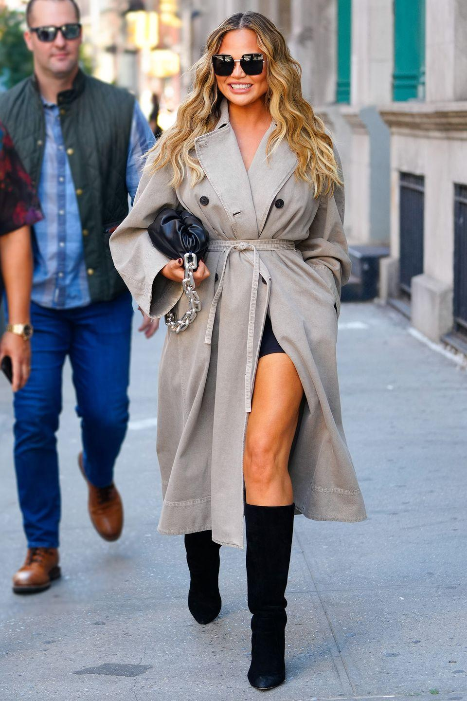 """<p><strong>27 September </strong></p><p>Chrissy Teigen dressed for autumn in a trench coat and knee-high boots.</p><p><a class=""""link rapid-noclick-resp"""" href=""""https://www.harpersbazaar.com/uk/fashion/what-to-wear/g16661706/best-trench-coats/"""" rel=""""nofollow noopener"""" target=""""_blank"""" data-ylk=""""slk:SHOP THE BEST TRENCH COATS"""">SHOP THE BEST TRENCH COATS</a></p>"""