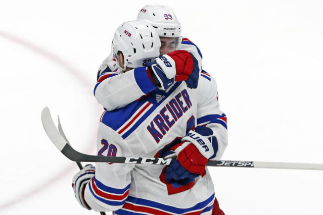 New York Rangers center Mika Zibanejad (93) embraces New York Rangers left wing Chris Kreider (20) after scoring the winning goal in overtime of an NHL hockey game against the New York Islanders, Tuesday, Feb. 25, 2020, in Uniondale, N.Y. The Rangers won 4-3. (AP Photo/Kathy Willens)