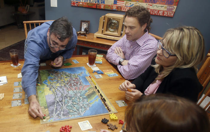 In this photo taken Thursday, Jan. 9, 2014, Spirit Airlines CEO Ben Baldanza left, Ted Christie, center, the airline's chief financial officer, and DeAnne Gabel, right, director Investor relations, right, play a game of Power Grid at Baldanza's home, in Fort Lauderdale, Fla. (AP Photo/Alan Diaz)