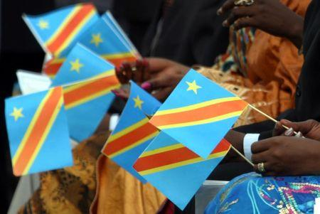 Congolese ladies hold paper replicas of Democratic Republic of Congo's new flag during ceremony in Kinshasa