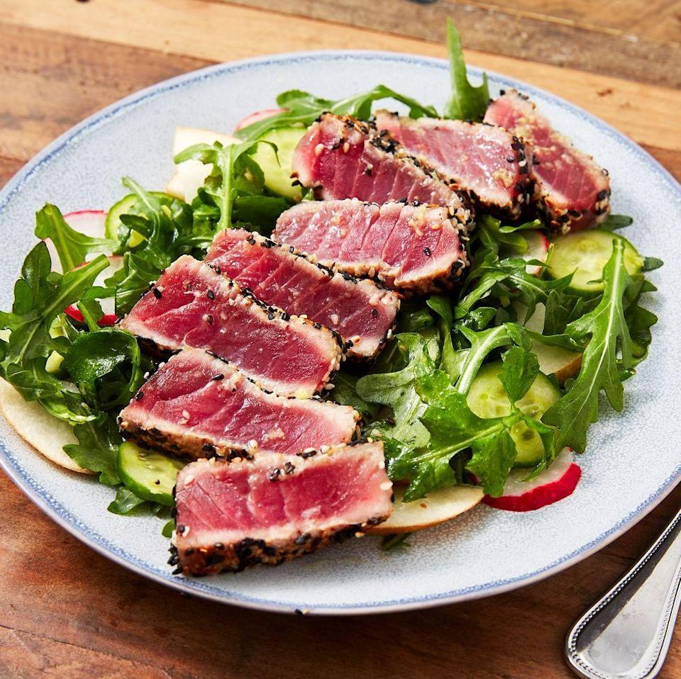 """<p>Turns out searing your own Ahi tuna at home is easy and <em>way</em> cheaper than that pricey Poke place. Peppery arugula and sweet pear bring tons of flavor to the tender fish.</p><p><em><a href=""""https://www.delish.com/cooking/recipe-ideas/a26554658/seared-ahi-tuna-steak-recipe/"""" rel=""""nofollow noopener"""" target=""""_blank"""" data-ylk=""""slk:Get the recipe from Delish »"""" class=""""link rapid-noclick-resp"""">Get the recipe from Delish »</a></em></p>"""