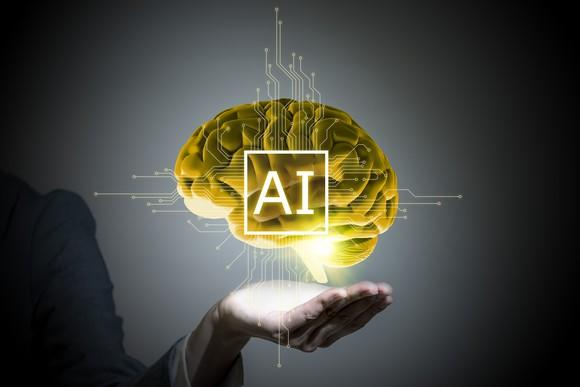 Image of human brain hovering over outstretched hand with AI superimposed over brain