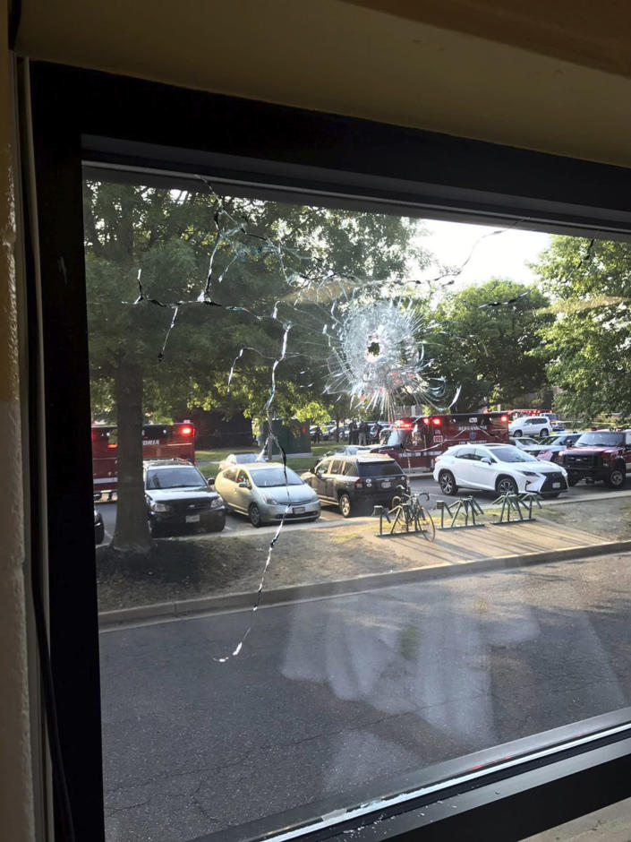 <p>Emergency personnel are seen through a window with a bullet hole in Alexandria, Va., Wednesday, June 14, 2017. House Majority Whip Steve Scalise of Louisiana and others were shot Wednesday at a congressional baseball practice, officials said. (Photo: Joseph Miscavige via AP) </p>