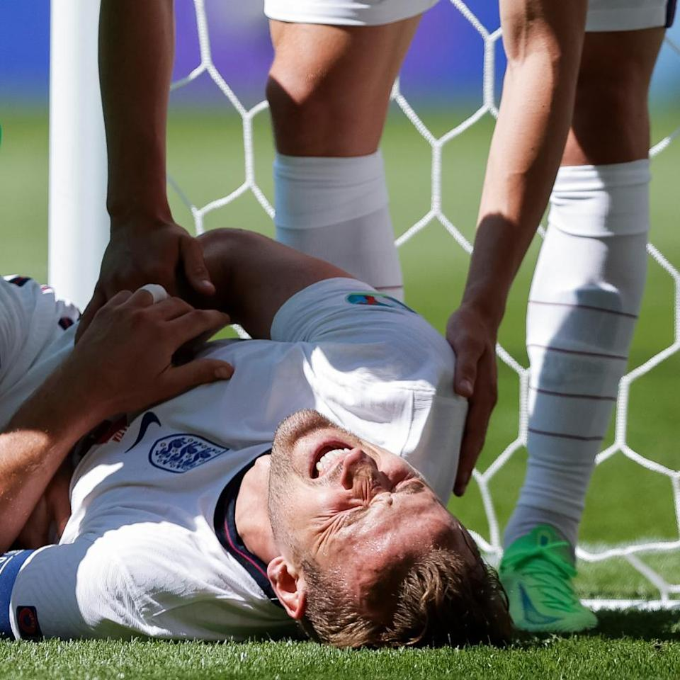 Harry Kane of England is winded after clattering into a post