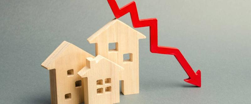 Miniature wooden houses and a red arrow down. The concept of falling interest rates.