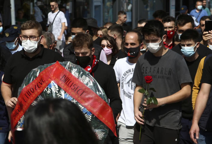 Young men carry a wreath and flowers while marching in silence to honor the victims in the burned out makeshift hospital in North Macedonia's northwestern town of Tetovo, Saturday, Sept. 11, 2021. Hundreds of people have marched Saturday in northwestern town of Tetovo to honor their 14 countrymen killed in a deadly fire that broke earlier this week and destroyed COVID-19 field hospital. (AP Photo/Boris Grdanoski)