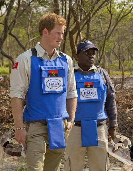 In this handout photo made available by the HALO Trust on Saturday, Aug. 17, 2013, Britain's Prince Harry, left, is given a tour around the current mine clearance site by HALO's provincial manager Tony Jose Antonio in Angola. Harry returned from Angola, where he visited a landmine clearance charity championed by his late mother, Princess Diana. The HALO Trust charity said Saturday the 28-year-old prince visited the Angolan town of Cuito Cuanavale, which saw heavy fighting during the southern African nation's 1975-2002 civil war. The group said Harry toured minefields and met beneficiaries of the group's work. (AP Photo/HALO Trust)