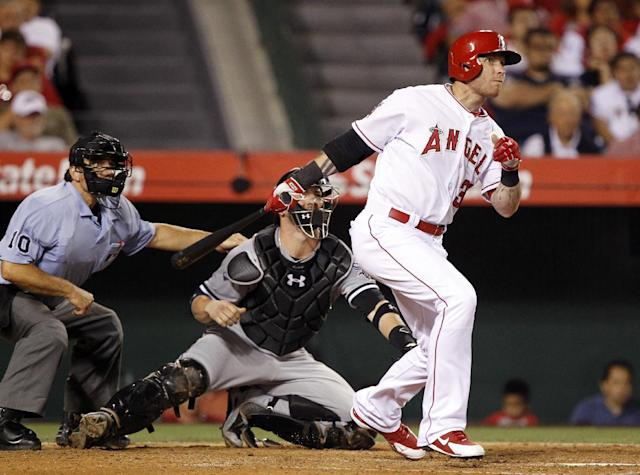 Los Angeles Angels designated hitter Josh Hamilton, right, hits a single to right field, with home plate umpire Phil Cuzzi, left, and Chicago White Sox catcher Tyler Flowers, center, watching in the fifth inning of a baseball game on Saturday, June 7, 2014 in Anaheim, Calif. (AP Photo/Alex Gallardo)