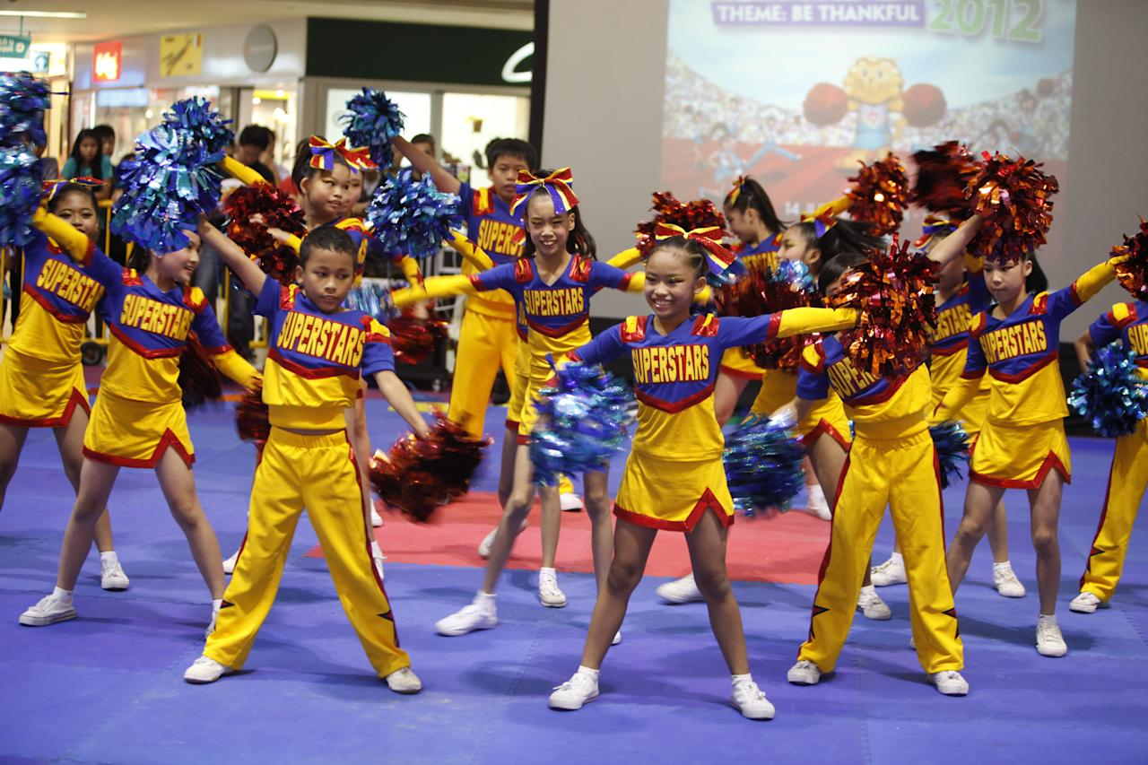 Winners from Si Ling Primary School perform a routine with red and blue pom poms.