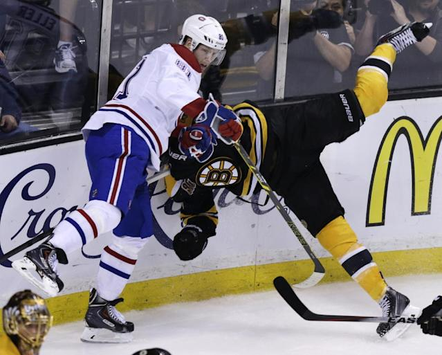 Boston Bruins defenseman Johnny Boychuk, right, is upended while chasing the puck against Montreal Canadiens center Lars Eller (81) during the first period of Game 5 in the second-round of the Stanley Cup hockey playoff series in Boston, Saturday, May 10, 2014. (AP Photo/Charles Krupa)