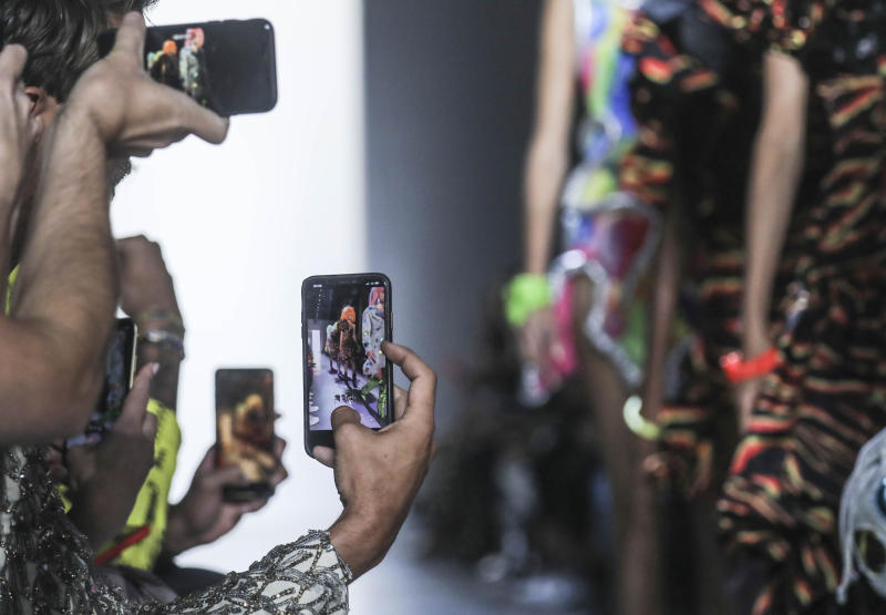 Guests grab cellphone photos of models in the latest fashion creation from Jeremy Scott, during New York's Fashion Week, Friday, Sept. 6, 2019. (AP Photo/Bebeto Matthews)